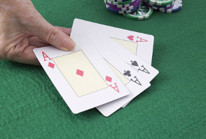 image of a man holding playing cards